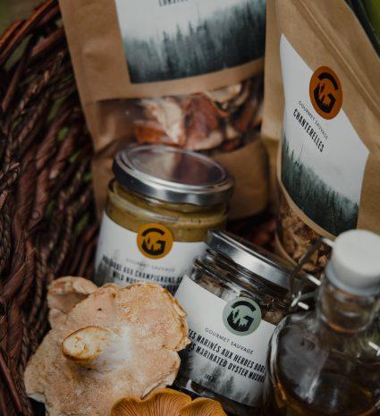 Panier en osier contenant différents produits : des champignons frais, champignons séchés, moutarde et marinade.